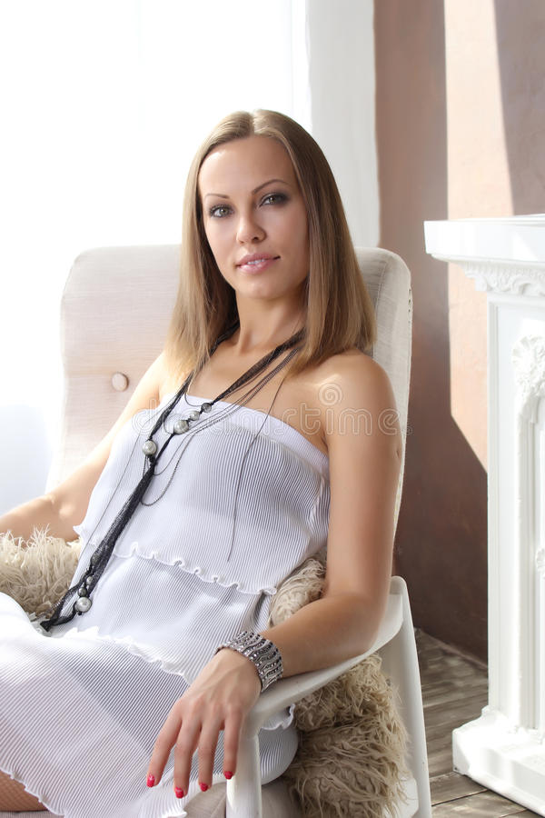 Mujer hermosa joven que se sienta en una silla fotos de archivo libres de regalías