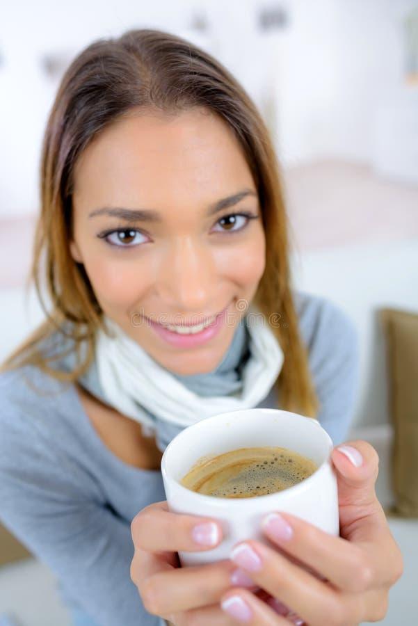 Mujer hermosa joven que sostiene el café de la taza imagen de archivo