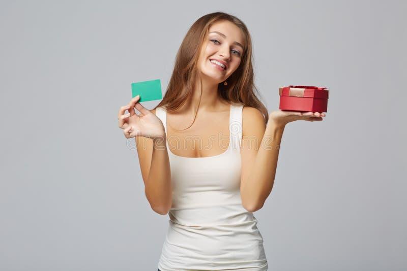 Mujer hermosa joven que sostiene la pequeña tarjeta roja de la caja y de crédito, encendido fotos de archivo