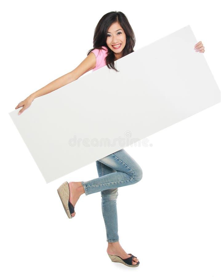 Mujer hermosa joven que sostiene la tarjeta blanca en blanco imagenes de archivo