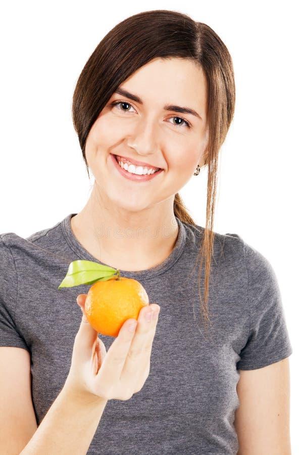 Mujer hermosa joven que sostiene las mandarinas frescas fotos de archivo