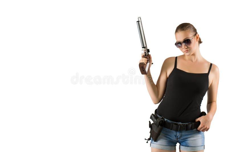 Mujer hermosa joven que sostiene un arma en el fondo blanco imágenes de archivo libres de regalías