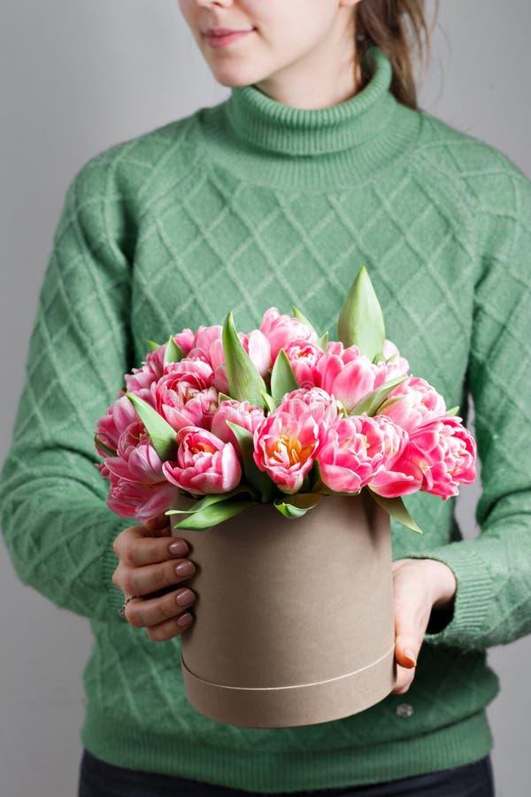 Mujer hermosa joven que sostiene un ramo de tulipanes en una caja de regalo colores rosados en un caja o ramo Presente el 8 de ma fotografía de archivo