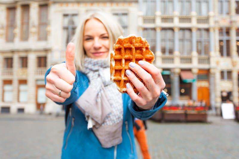 Mujer hermosa joven que sostiene una galleta belga tradicional en el fondo de la gran plaza del mercado en Bruselas foto de archivo