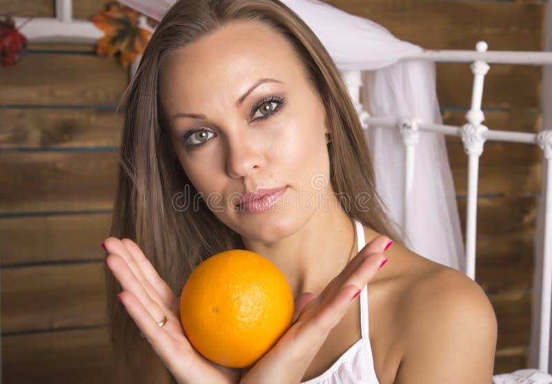 Mujer hermosa joven que sostiene una naranja con dos manos Retrato fotografía de archivo libre de regalías