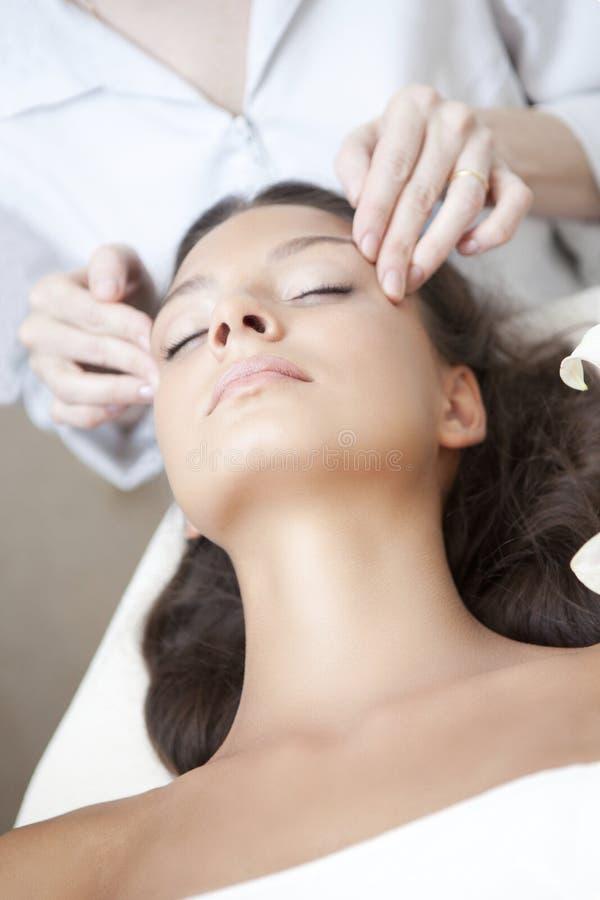 Mujer hermosa joven que tiene masaje facial fotos de archivo