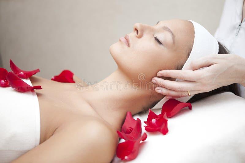 Mujer hermosa joven que tiene masaje facial imagenes de archivo
