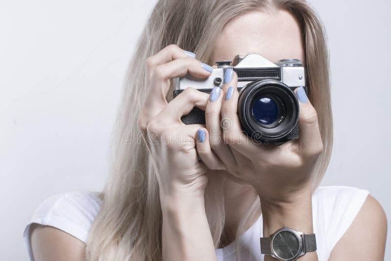 Mujer hermosa joven que toma una foto con una cámara retra imágenes de archivo libres de regalías