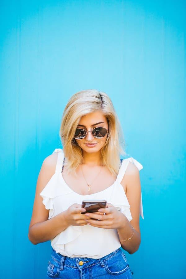 Mujer hermosa joven que usa el estudio del teléfono móvil en fondo azul del color fotografía de archivo