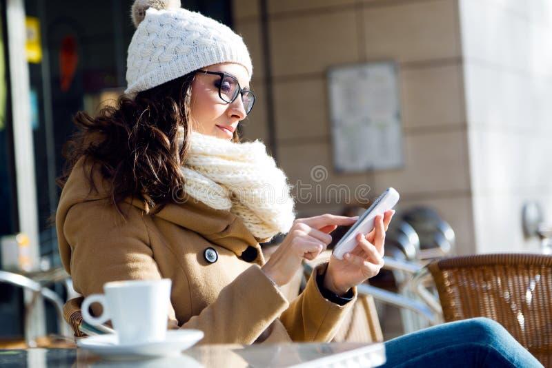 Mujer hermosa joven que usa su teléfono móvil en un café imagen de archivo libre de regalías