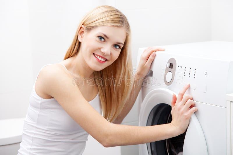 Mujer hermosa joven que usa una lavadora fotos de archivo
