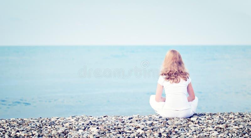 Mujer hermosa joven sola triste que se sienta cómodamente en la playa el mar imágenes de archivo libres de regalías