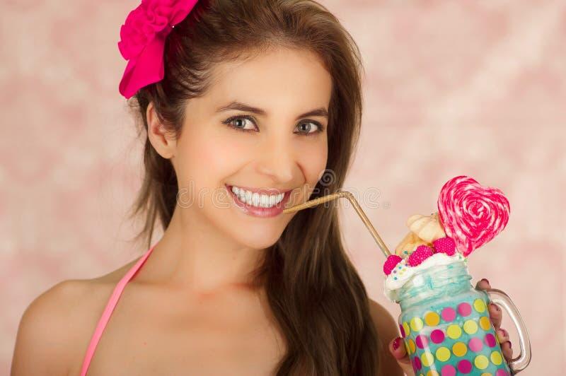 Mujer hermosa joven sonriente, llevando una maleta rosada, llevando a cabo un batido de leche azul sabroso en la moda del estudio foto de archivo libre de regalías