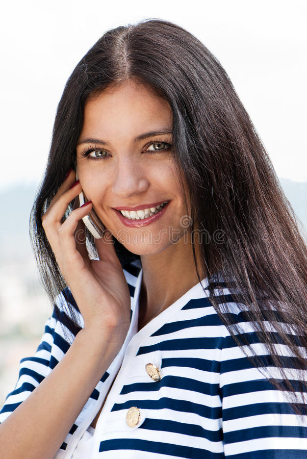 Mujer hermosa joven sonriente que habla en c fotografía de archivo libre de regalías