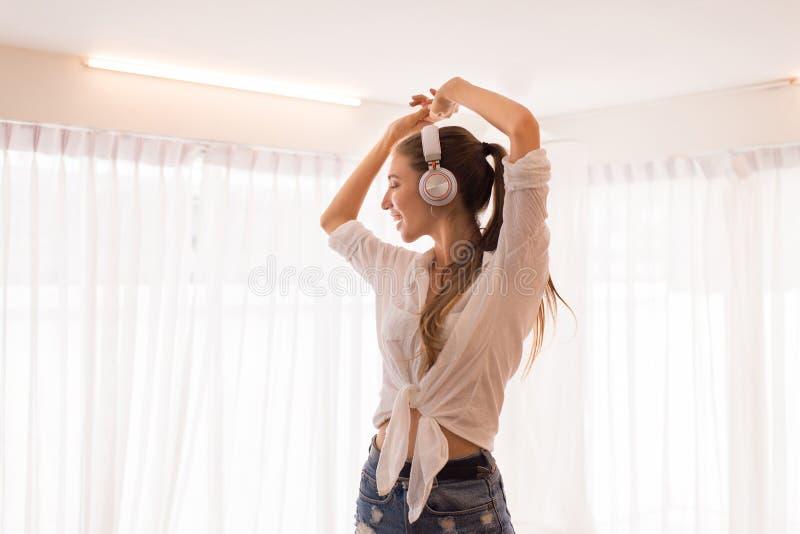 Mujer hermosa joven usando el auricular y el escuchar la música y la danza en dormitorio, tiempo, feliz de relajación y sonrisa imagen de archivo libre de regalías