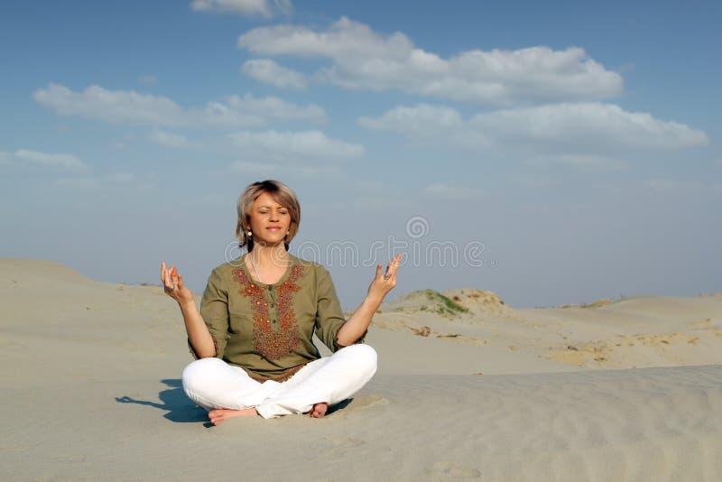 Mujer hermosa meditating en desierto fotos de archivo libres de regalías