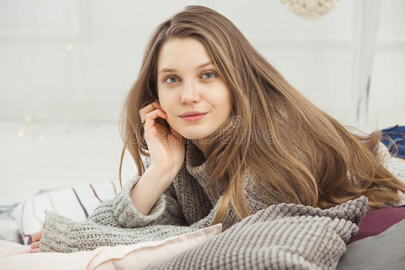 Mujer hermosa ningún maquillaje que miente en la almohada en suéter hecho punto imagen de archivo libre de regalías