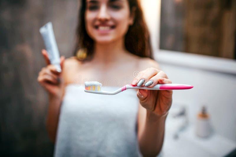 Mujer hermosa oscuro-cabelluda deportiva joven que hace rutina de la tarde de la mañana en el espejo Goma de diente modelo agrada foto de archivo libre de regalías