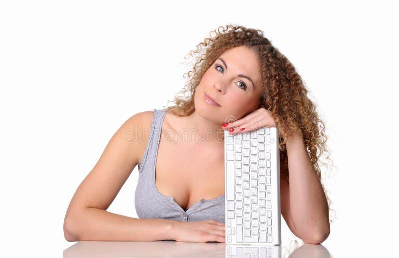 Mujer hermosa, pelo rizado rojo, sentándose en un escritorio con el teclado fotografía de archivo