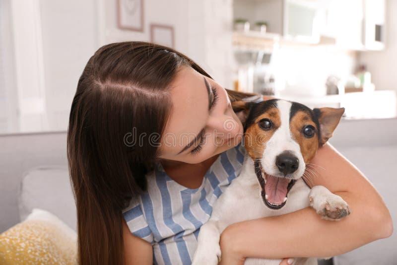 Mujer hermosa que abraza su perro en el sofá imagenes de archivo