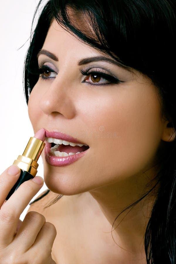 Mujer hermosa que aplica el lápiz labial fotos de archivo libres de regalías
