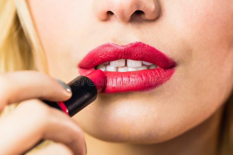 Mujer hermosa que aplica el lápiz labial rojo en los labios contra fondo negro foto de archivo