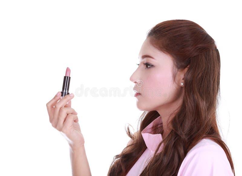 Mujer hermosa que aplica el lápiz labial rosado fotografía de archivo