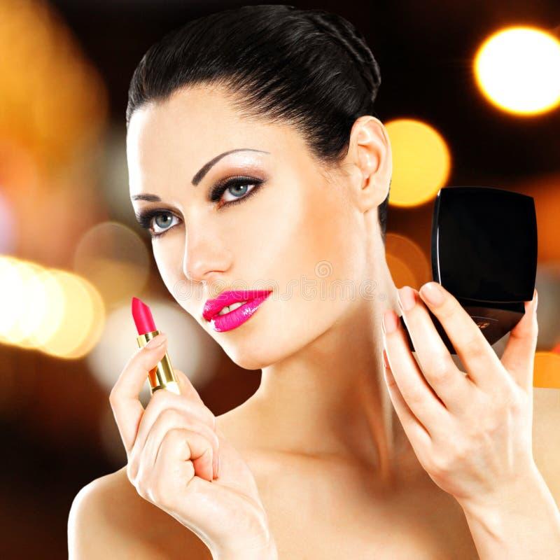 Mujer hermosa que aplica el lápiz labial rosado en los labios fotografía de archivo
