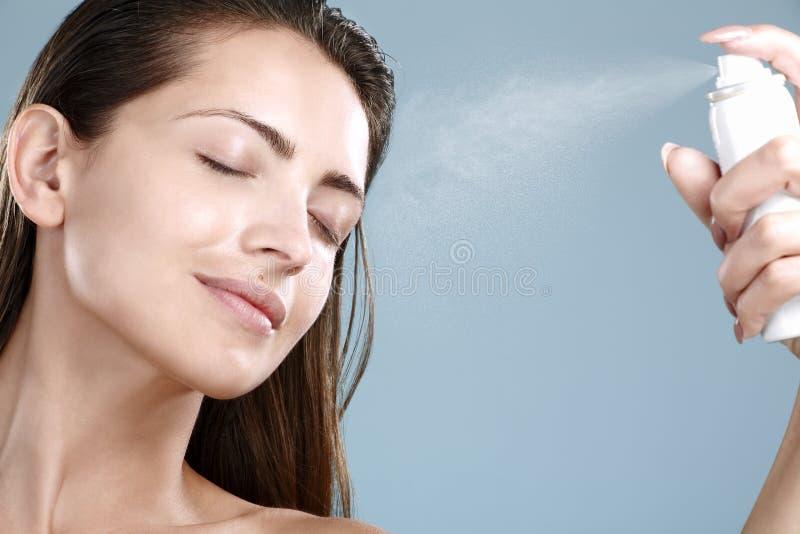 Mujer hermosa que aplica el tratamiento de aguas del espray en cara fotografía de archivo libre de regalías