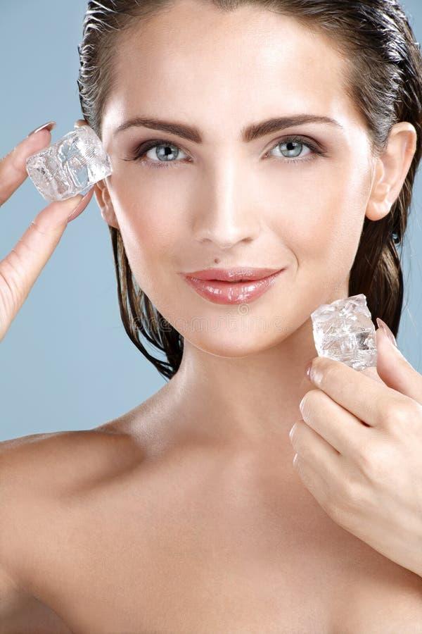 Mujer hermosa que aplica el tratamiento del cubo de hielo en cara imagenes de archivo
