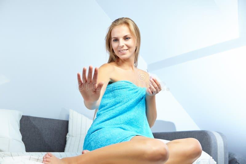 Mujer hermosa que aplica esmalte de uñas rojo foto de archivo libre de regalías