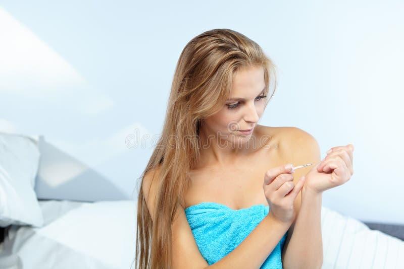 Mujer hermosa que aplica esmalte de uñas rojo imagen de archivo