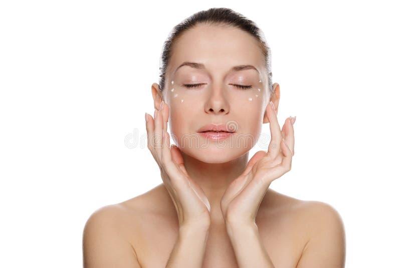 Mujer hermosa que aplica la crema cosmética fotos de archivo