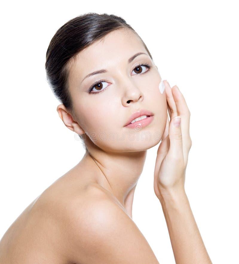 Mujer hermosa que aplica la crema cosmética en cara fotografía de archivo libre de regalías