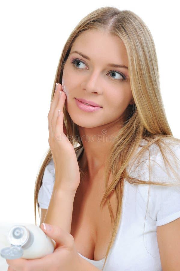 Mujer hermosa que aplica la crema en su mejilla fotografía de archivo libre de regalías