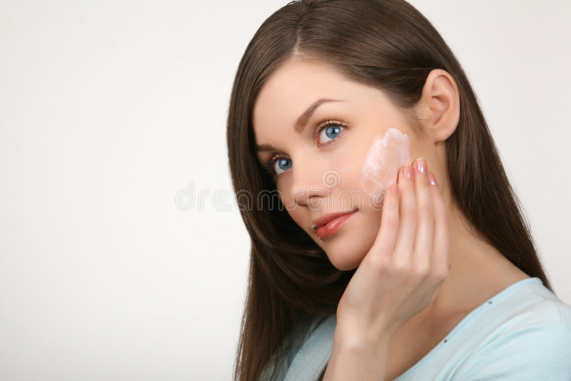Mujer hermosa que aplica la crema a la cara fotografía de archivo libre de regalías