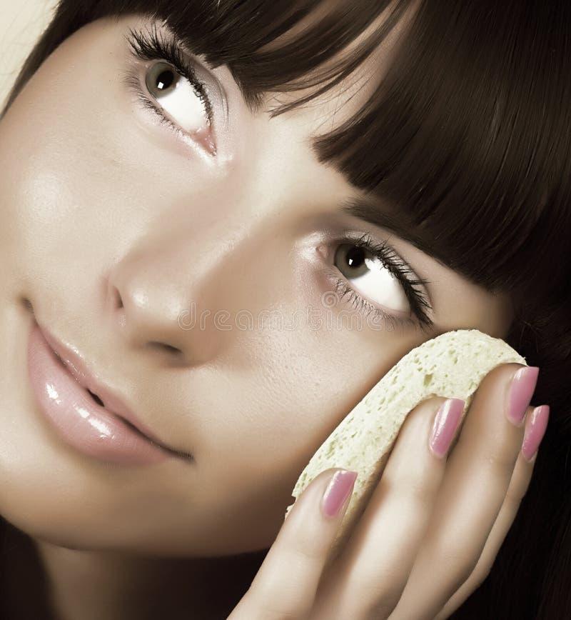 Mujer hermosa que aplica la nata imagenes de archivo