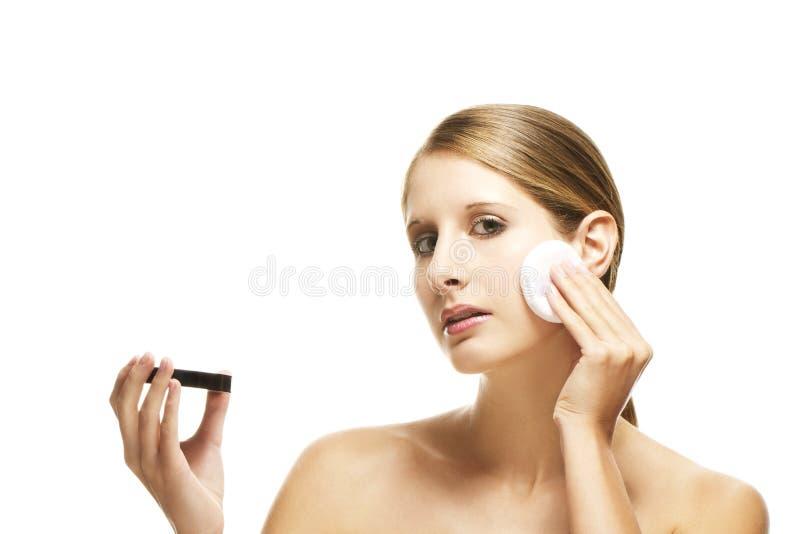 Mujer hermosa que aplica maquillaje fotografía de archivo libre de regalías