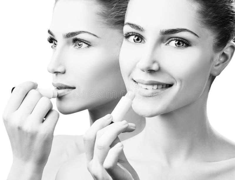 Mujer hermosa que aplica protector labial higiénico imagen de archivo libre de regalías
