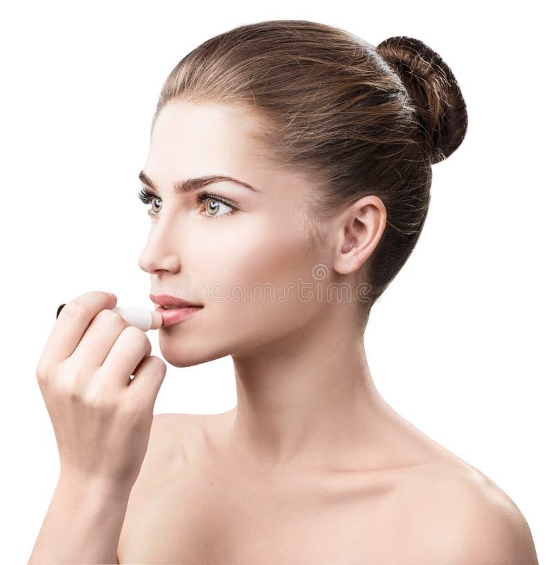 Mujer hermosa que aplica protector labial higiénico fotos de archivo