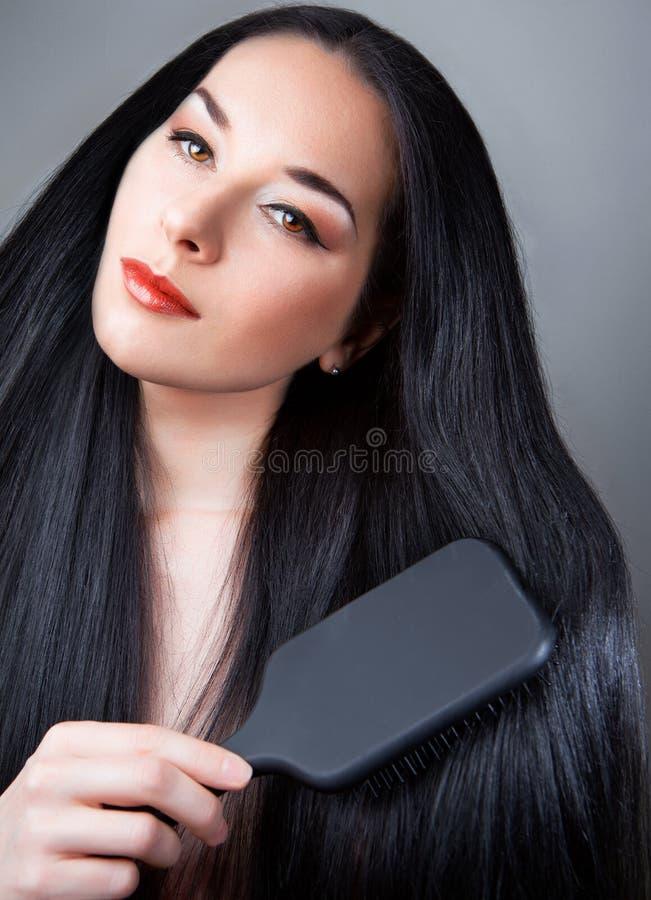 Mujer hermosa que aplica su pelo con brocha fotos de archivo