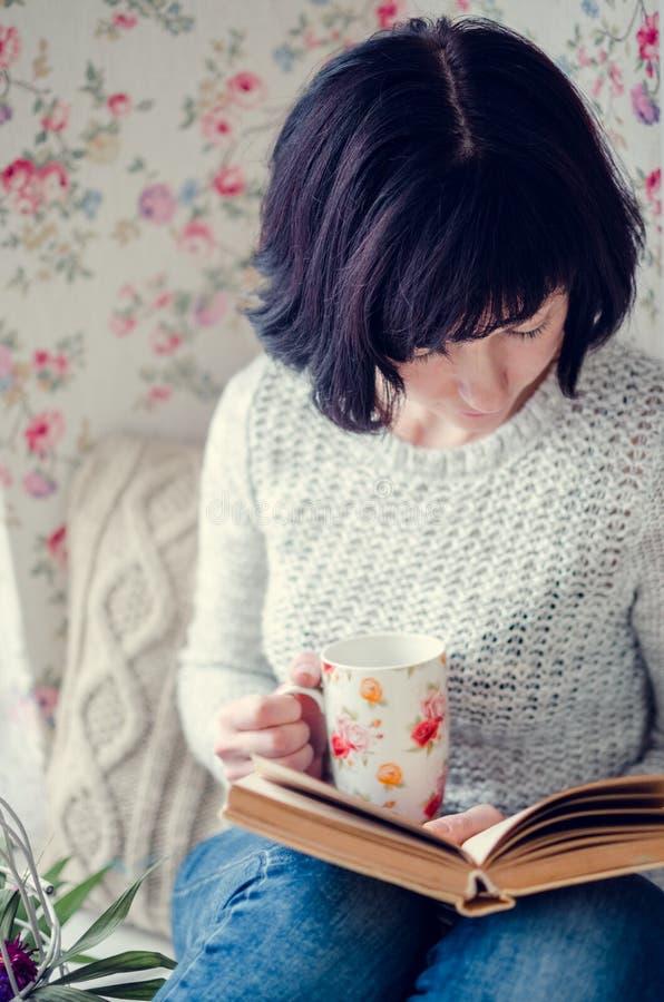 Mujer hermosa que bebe té caliente y que lee un libro fotografía de archivo libre de regalías