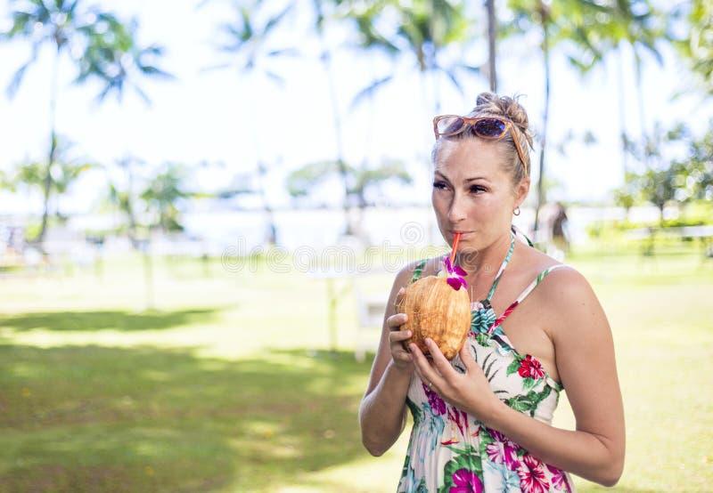 Mujer hermosa que bebe un cóctel en un coco en vacaciones de Hawaii fotos de archivo