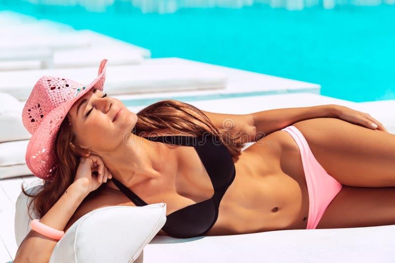 Mujer hermosa que broncea en la piscina imagenes de archivo