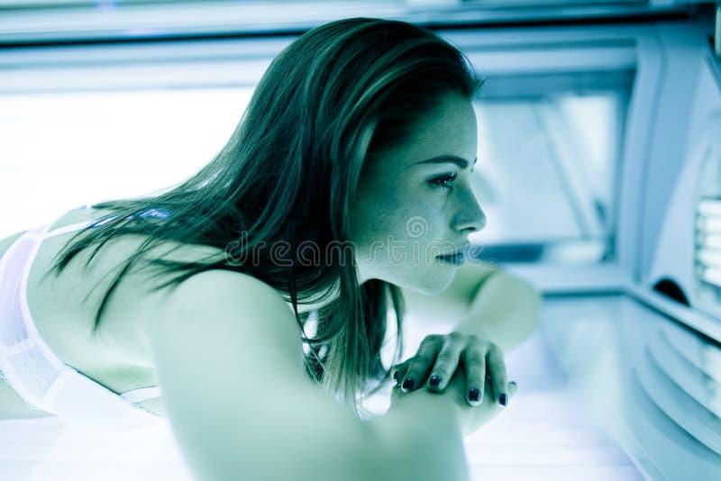 Mujer hermosa que broncea en solarium fotografía de archivo libre de regalías