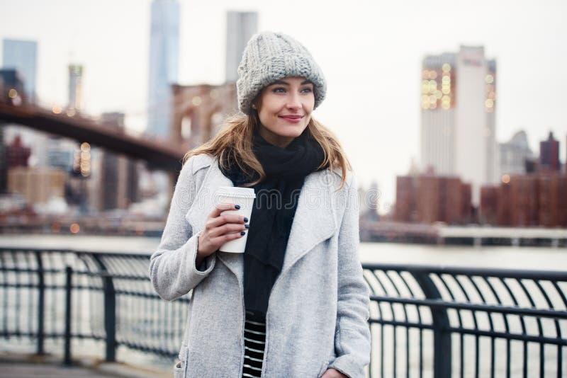 Mujer hermosa que camina con una taza de café en New York City imágenes de archivo libres de regalías