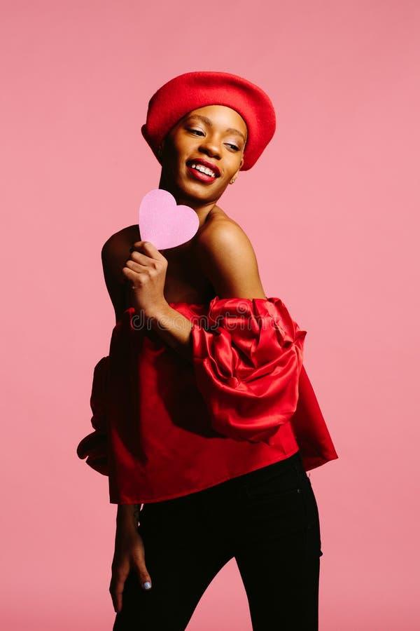 Mujer hermosa que celebra el corazón y la sonrisa rosados fotos de archivo