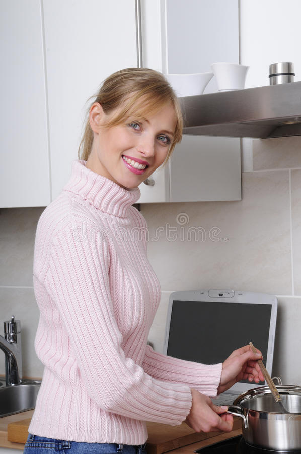 Mujer hermosa que cocina en una cocina moderna imagen de archivo libre de regalías