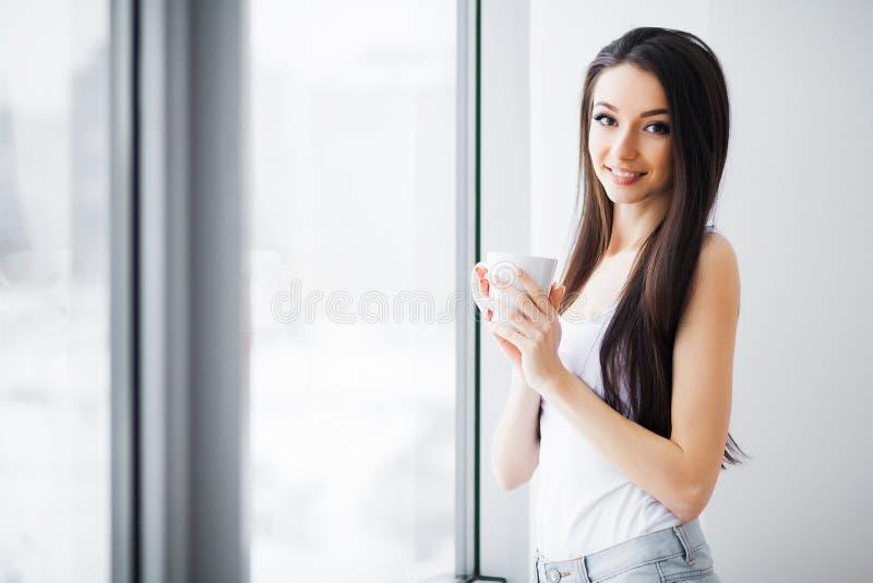 Mujer hermosa que coloca ventanas cercanas Ma?ana hermosa imagenes de archivo