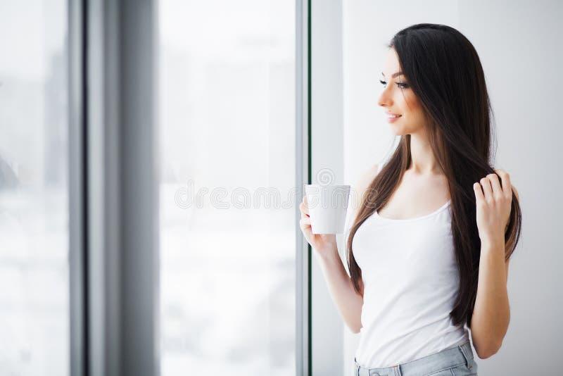 Mujer hermosa que coloca ventanas cercanas Ma?ana hermosa imagen de archivo libre de regalías